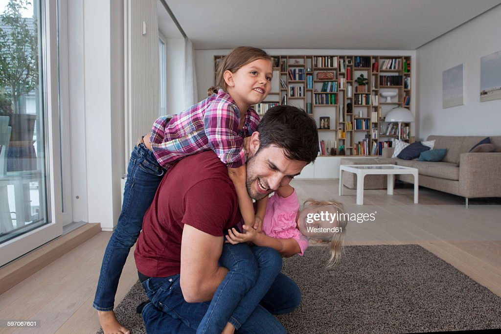 Man playing with his little daughters in the living room : Stock Photo