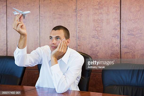 Man playing with miniature aeroplane at boardroom table