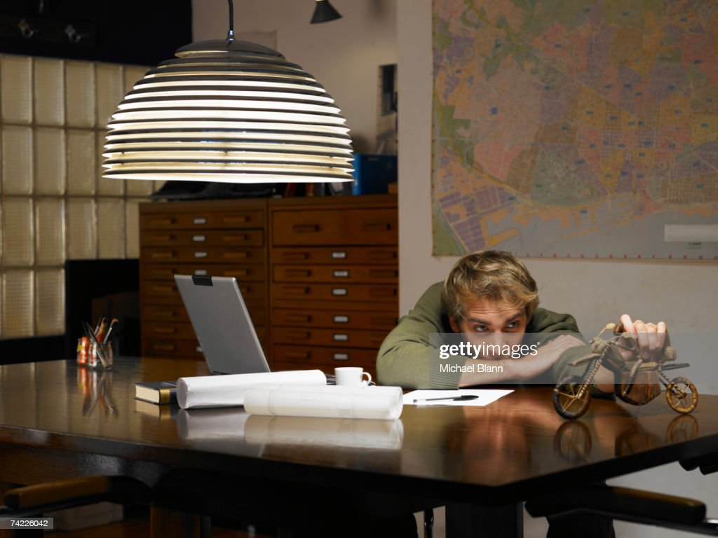 Man playing with model motorcycle at desk in office : Stock Photo