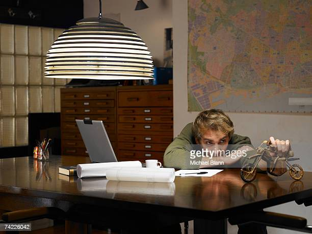 man playing with model motorcycle at desk in office - wasting time stock pictures, royalty-free photos & images