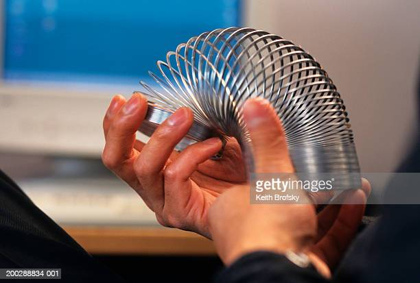 man playing with slinky, close-up of hands - metal coil toy stock photos and pictures