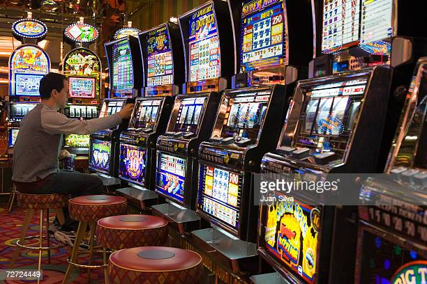 Man playing with slot machines in casino