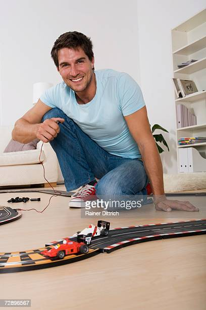 Man playing with toy racetrack, smiling, portrait