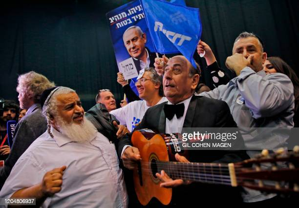 Man plays a guitar as others around him wave Likud party flags and show its election signs with the face of its leader Prime Minister Benjamin...