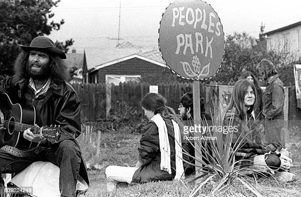 A man plays a guitar as others surround a sign that says People's Park circa 1970 in Berkeley California