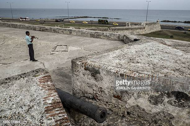 A man plays a trumpet at the historic fortress walls of Cartagena Colombia on September 8 2014 The city of Cartagena celebrated on Monday the 400th...