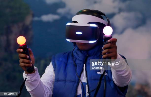 "Man plays a video game with a virtual reality head-mounted headset ""PlayStation VR"" developed by Sony Interactive Entertainment during the 'Paris..."
