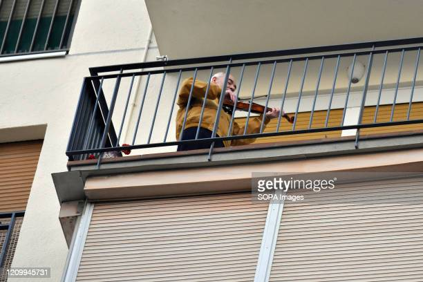 L´HOSPITALET BARCELONA SPAIN A man plays a violin from his terrace applauding Covid19 fighters during confinement 00 pm continue to applaud showing...