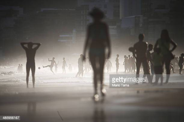 A man plays altinha a spinoff of soccer played on the beach as others gather on Ipanema Beach in a lowlying mist on April 21 2014 in Rio de Janeiro...
