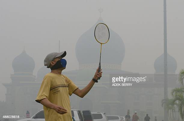 A man plays badminton while wearing a face mask in the grounds of the AnNur Great Mosque as haze shrouds the Sumatran city of Pekanbaru in Riau...