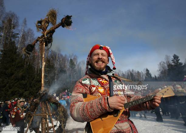 A man plays balalaika as Maslenitsa straw effigy burns during the celebration of Maslenitsa also know as Shrovetide or Butter Week held to mark the...