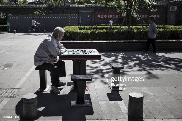 A man plays Chinese chess while sitting in a park in a traditional hutong neighborhood in Beijing China on Sunday May 14 2017 Chinas economy is...
