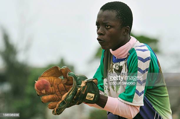 A man plays cricket on November 15 2012 in Freetown at Kingtom Oval Sierra Leone's only cricket oval Packed with hard red dirt overlooked by a faded...