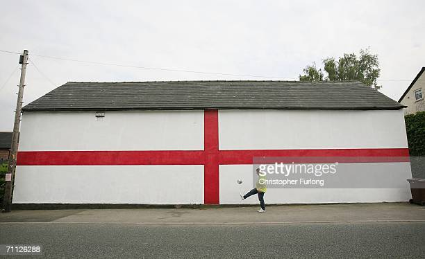 Man plays football next to a giant flag of St George that has been painted on the side of a house on 5 June Lostock Gralam, England. As World Cup...