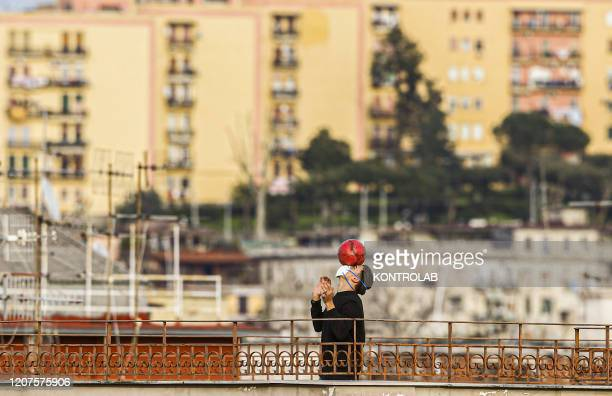 Man plays football wearing a protective mask on a roof after a Government Decree declaring all of Italy a protected area to combat covid-19 -...