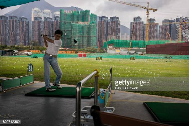 A man plays golf as residential buildings stand in front of the golf course on April 5 2017 in Hong Kong Hong Kong Hong Kong is marking 20 years...