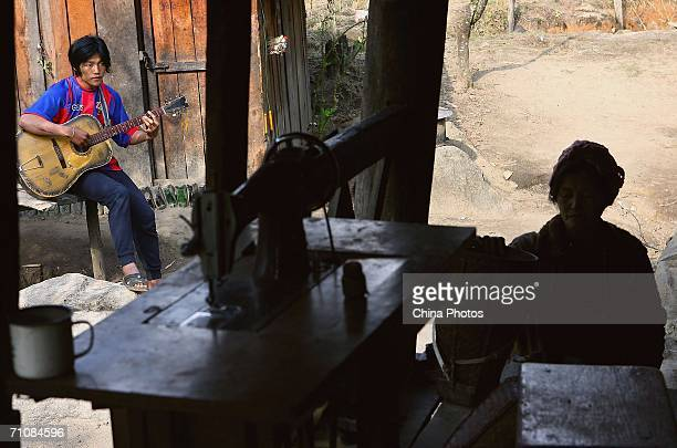 A man plays Guitar as his mother does needlework at a village on March 18 2006 in Panwa Kachin State Special Region 1 of Kachin State Myanmar The...