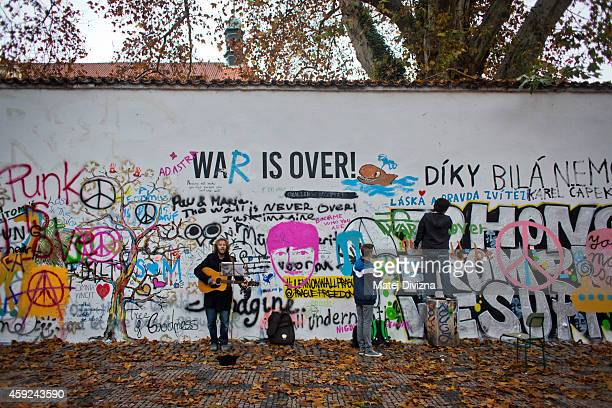 A man plays guitar as men paint graffiti on the memorial wall dedicated to former Beatle musician John Lennon on November 19 2014 in Prague Czech...
