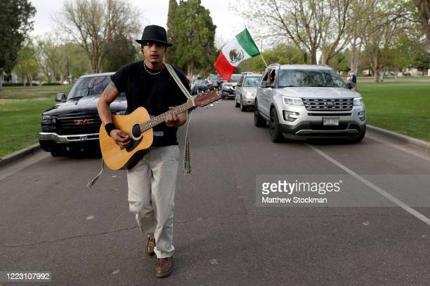 Man plays guitar as revelers cruise through Mineral Palace Park in celebration of Cinco de Mayo on May 05, 2020 in Pueblo, Colorado. Most traditional...