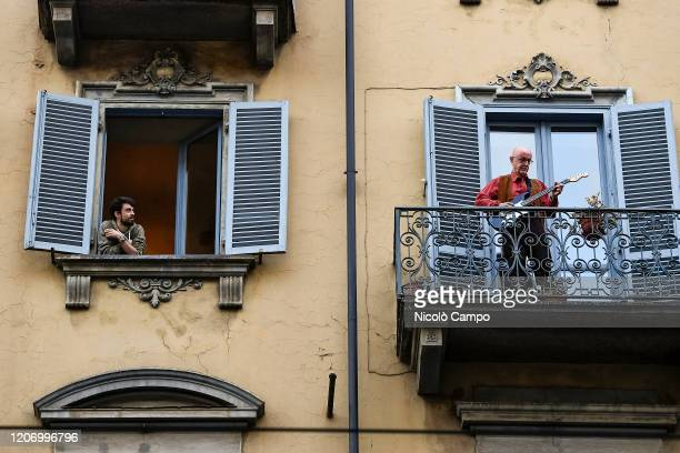 A man plays guitar from the balcony of his home as a man looks at him in the neighborhood San Salvario during a flash mob launched throughout Italy...