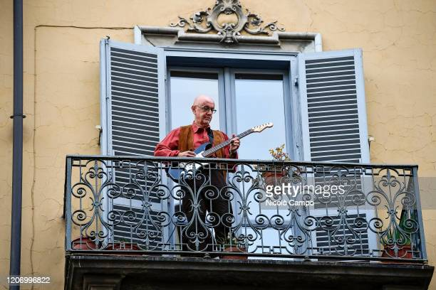 Man plays guitar from the balcony of his home in the neighborhood San Salvario during a flash mob launched throughout Italy to bring people together....