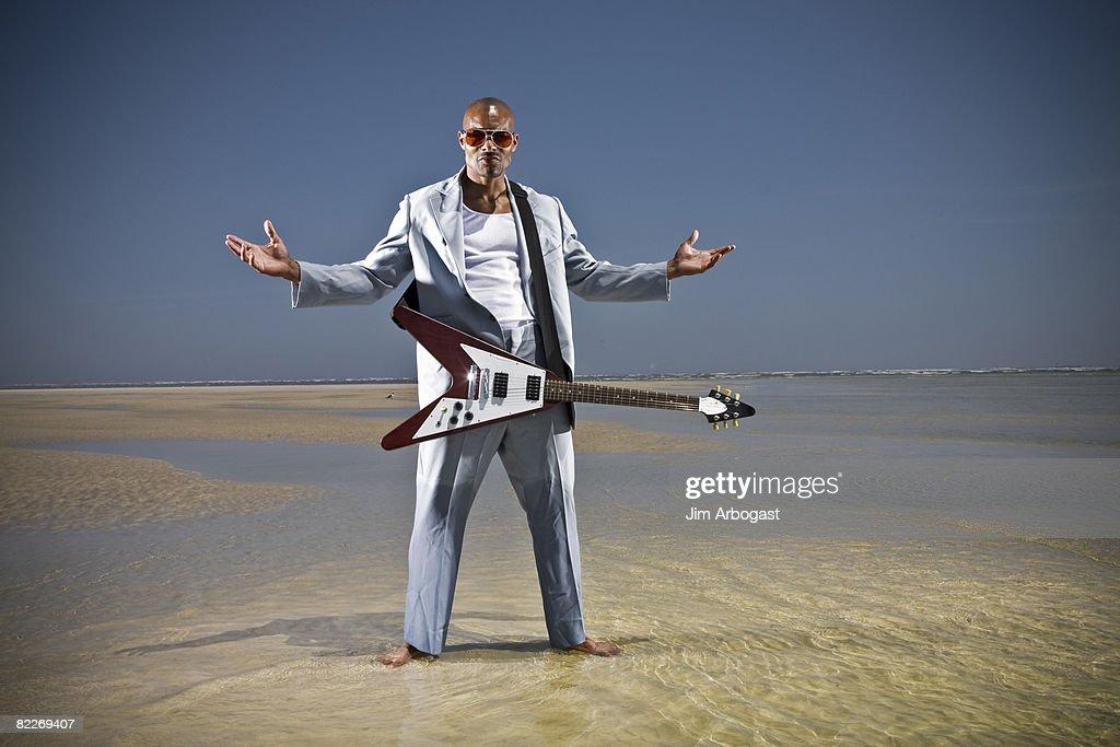 A man plays guitar on beach. : Stock Photo