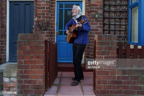 A man plays guitar outside his house as residents of Leven Street in Saltburn By The Sea gather in their doorways front gardens and street outside...