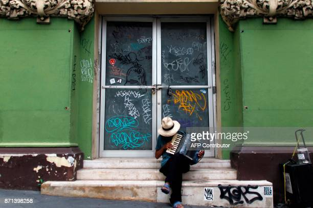 A man plays his accordion in front of a closed down business in Old San Juan Puerto Rico on November 7 2017 The Center for Puerto Rican Studies at...