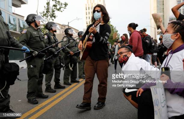 A man plays his guitar during a protest for the killing of George Floyd in front of Santa Clara County Sheriffs officers and San Jose Police officers...
