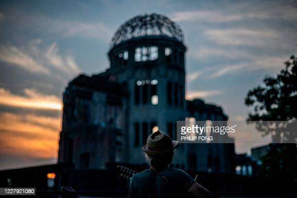 TOPSHOT A man plays his guitar in front of in front of ruins of the Hiroshima Prefectural Industrial Promotion Hall now commonly known as the atomic...