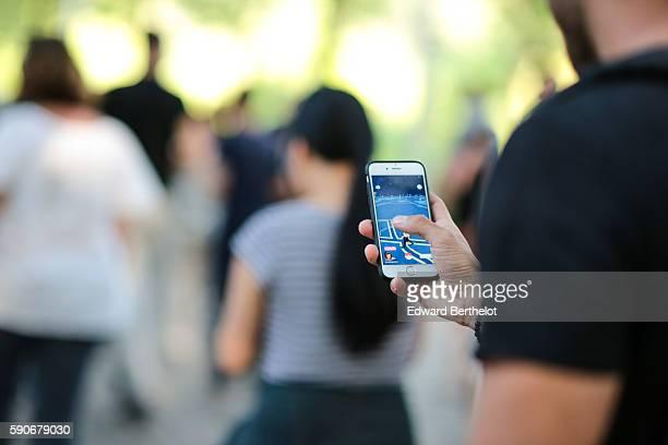 A man plays Nintendo Co's Pokemon Go augmentedreality game at the Parc de la Villette on August 17 2016 in Paris France His smartphone screen...