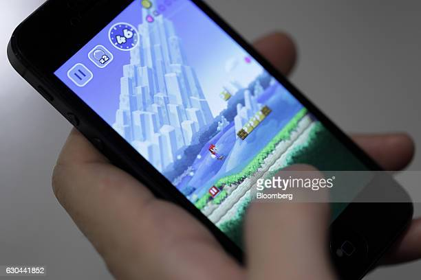 A man plays Nintendo Co's Super Mario Run mobile game on an Apple Inc iPhone in this arranged photograph in Tokyo Japan on Thursday Dec 22 2016 The...