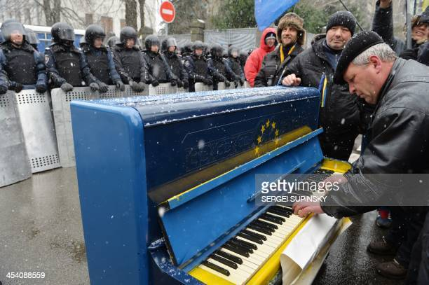 A man plays on a piano decorated with EU flag in front of riot police as protesters picket Viktor Yanukovych's presidential office in Kiev on...
