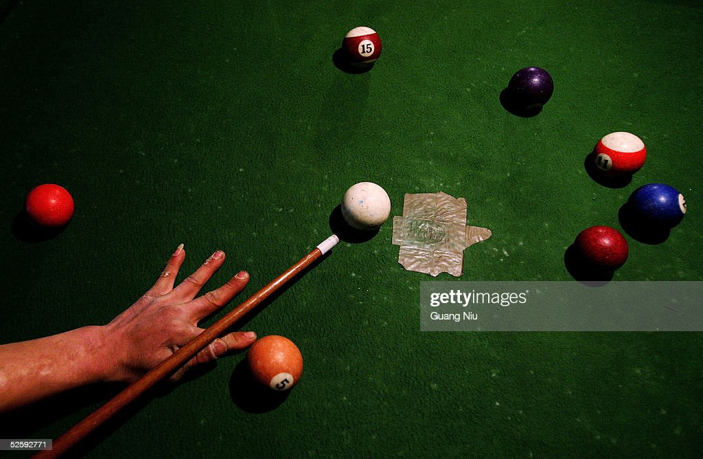 A Man Plays On An Outdoor Pool Table In The Evening On April 5, 2005