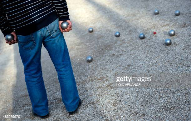 A man plays petanque at the Luxembourg Gardens in Paris on March 5 2015 AFP PHOTO / LOIC VENANCE