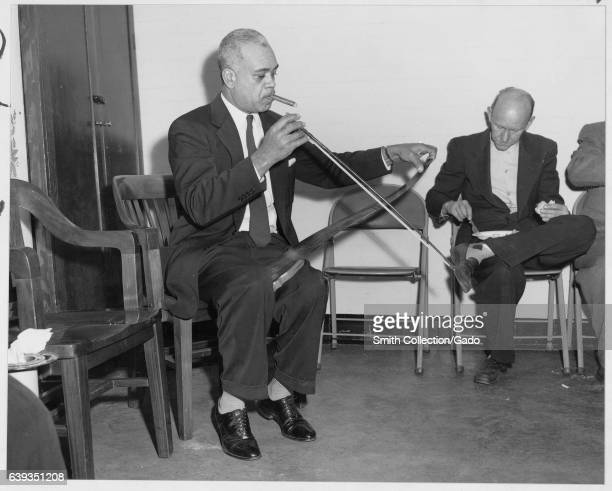 A man plays saw at the National Archives Christmas Party College Park Maryland 1960