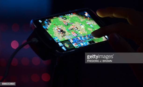 A man plays 'tales Craft' from BR Games on cellphone on day two of E3 2017 the three day Electronic Entertainment Expo at the Los Angeles Convention...