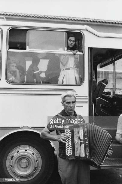 A man plays the accordion outside a coach filled with passengers Algarve Portugal 1985