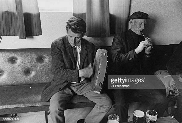 A man plays the bodhran whilst another man plays the penny whistle in a pub Ireland 1974