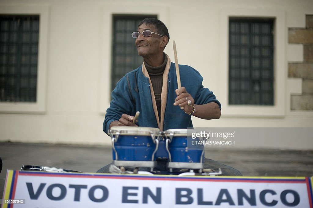 A man plays the bongo behind a sign urging to vote in blank at Bolivar square in downtown Bogota on May 29, 2010. Colombia will hold presidential elections on Sunday, in which nine candidates will be whittled down to just two -- likely Santos and Mockus -- in a knockout round on June 20. AFP PHOTO/Eitan Abramovich