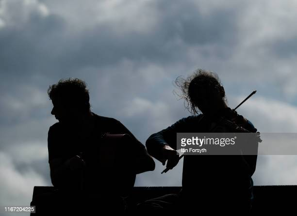 A man plays the fiddle as he sits on a bench during the annual Whitby Regatta on August 10 2019 in Whitby England At over 170 years old the Whitby...