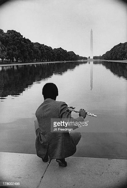 A man plays the flute at the edge of the 'Lincoln Memorial Reflecting Pool' during the Poor People's Campaign protest Washington DC May 1968