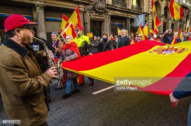 A man plays the national anthem of Spain with his saxophone to the Spanish flag during the unionist demonstration for the unity of SpainSpain...
