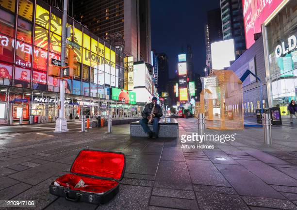 A man plays the saxophone in an empty Times Square on April 24 2020 in New York City Due to stayathome orders in New York the New York streets...