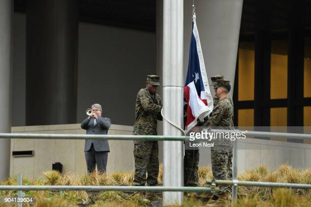 A man plays the 'Star Spangled Banner' as soldiers raise the American flag at the new US embassy for the first time on January 12 2018 in London...