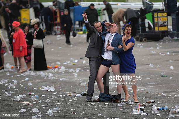 A man plays to the cameras as racegoers make their way home at the end of Ladies Day the second day of the Aintree Grand National Festival meeting on...