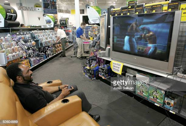 A man plays video games at a Best Buy store April 8 2005 in San Francisco California Nielsen Entertainment said on Thursday that men spend more money...