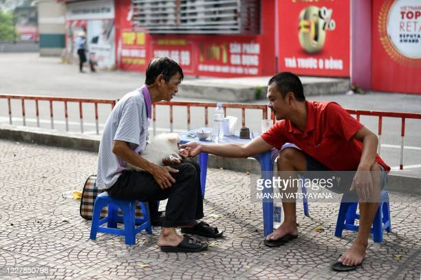Man plays with a dog on a street in Hanoi on July 31, 2020.