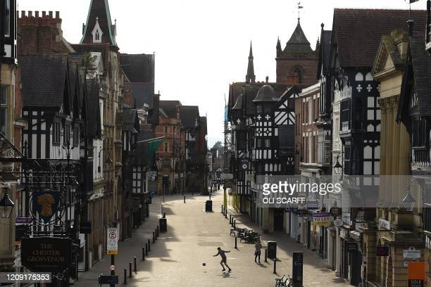 Man plays with a football on Eastgate Street in a near-deserted Chester city centre in north-West England on April 5, 2020 as the warm weather tests...