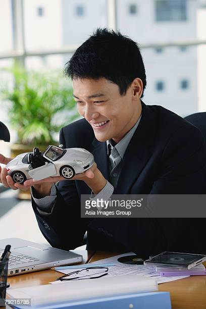 A man plays with a toy car on his desk